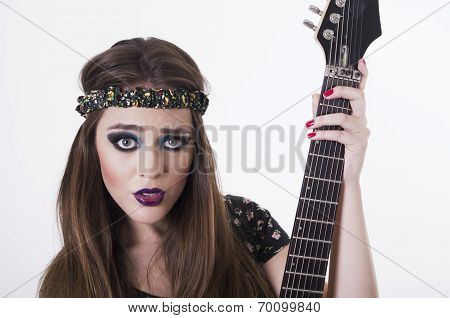 Beautiful rocker punk girl with colorful makeup holding electric guitar