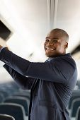 happy african businessman putting luggage into overhead locker on airplane poster