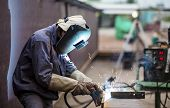Worker with protective mask welding metal in factory poster