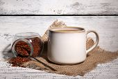 Cup of tasty rooibos tea, on old white wooden table poster