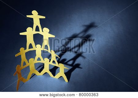 Human team pyramid on blue background