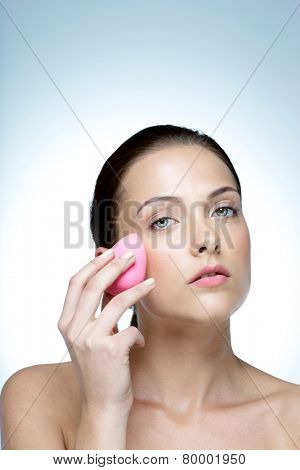 Woman applying foundation by sponge on face for make-up