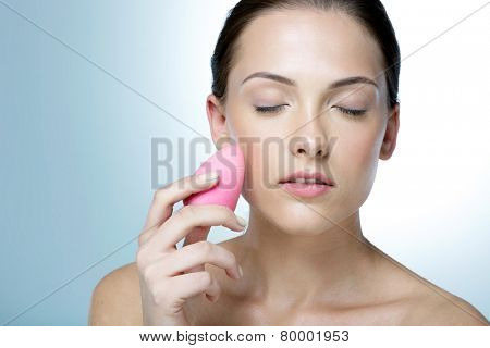 Attractive woman applying foundation by sponge on face for make-up