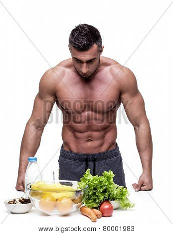 Pensive muscular man leaning on the table with healthy food