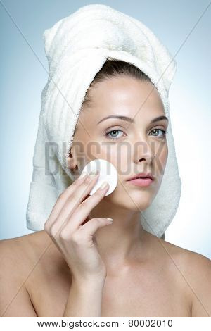 Portrait of a beautiful woman cleaning her face with cosmetic wad