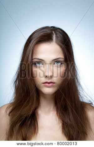 Closeup portrait of a beautiful woman over blue background