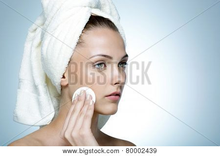 Portrait of attractive woman cleaning her face