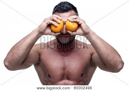 Happy muscular man holding oranges in front of his eyes