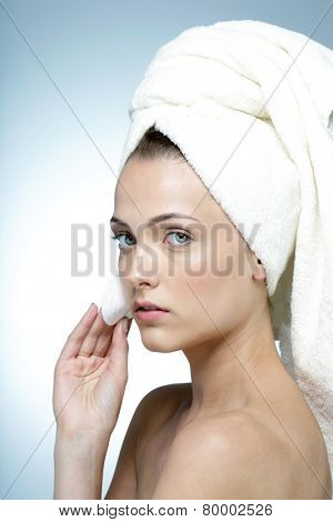 Portrait of cute young girl cleaning her face with cosmetic wad