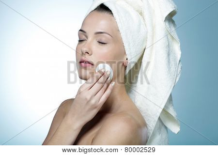 Portrait of a beautiful woman cleaning her face