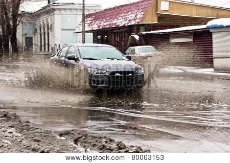 Dirty Water Splash From The Car Wheels At Spring Snowy Street
