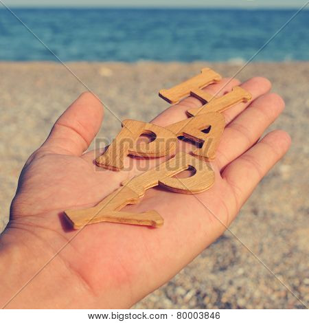 the hand of a young man showing wooden letters forming the word happy, on the beach, with a filter effect