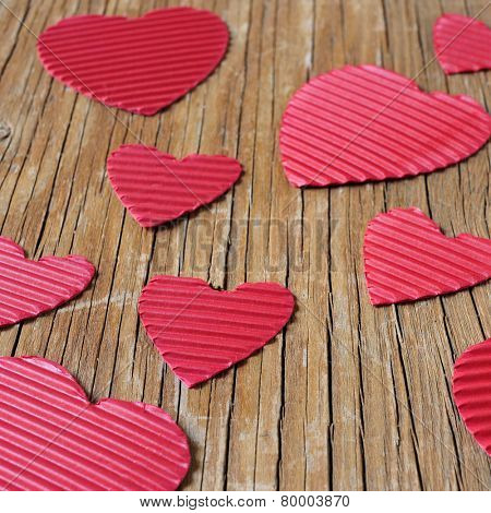 some red hearts of different sizes on a rustic wooden surface