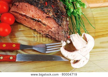 grilled beef sliced on transparent plate over wood