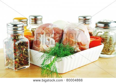 raw uncooked legs on wooden plate over white