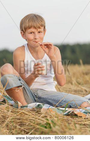 Teenage boy holding glass of milk and straw