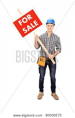 Full length portrait of a young male engineer holding a for sale sign isolated on white background