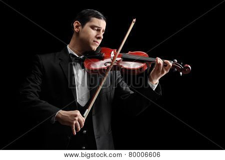 Studio shot of a classical violinist playing a violin on black background