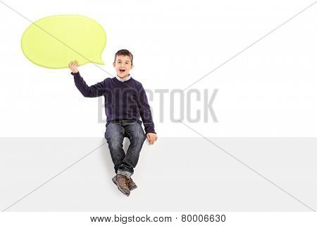 Male kid holding a speech bubble seated on panel isolated on white background