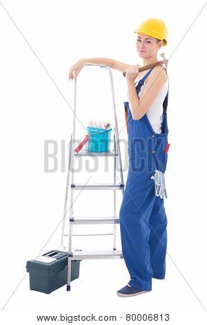Young Woman In Blue Coveralls With Builder's Tools And Ladder Isolated On White