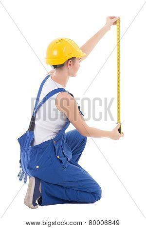 Back View Of Sitting Woman Builder Measuring Something With Measure Tape Isolated On White