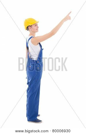 Side View Of Young Woman Builder Pointing At Something Isolated On White
