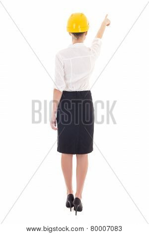 Rear View Of Business Woman Architect In Yellow Builder Helmet Pointing At Something Isolated On Whi