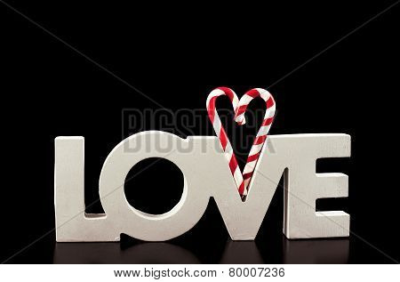 Large Letters Love And Heart Lollipop Isolated On Black - Stock Image