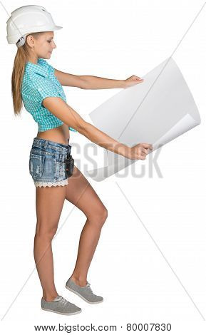 Beautiful woman builder holding in front of him large paper sheet