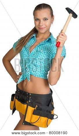 Smiling pretty girl in shorts, shirt and tool belt holding hammer near head