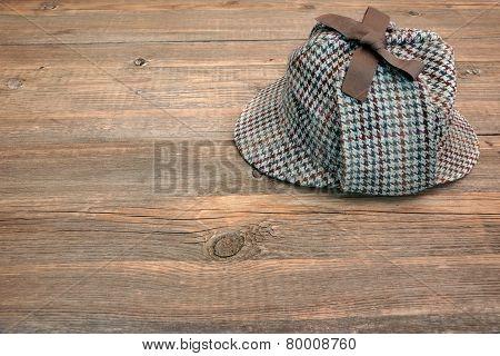 Deerstalker Or Sherlock Hat On Wooden Table
