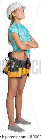 Looking up pretty girl in helmet, shorts, shirt and tool belt with tools. Full length