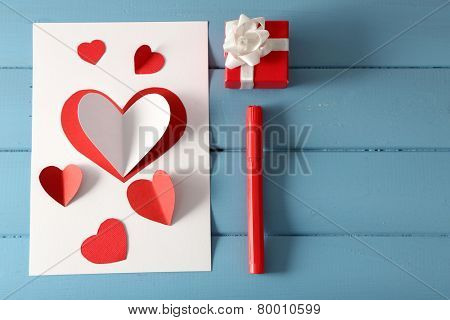 Beautiful hand made post card and pen on color wooden background