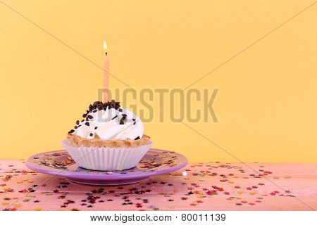 Birthday cup cake with candles on plate on color wooden table and orange background