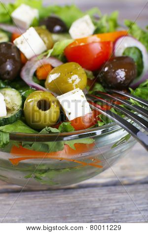 Greek salad in glass dish with fork, closeup