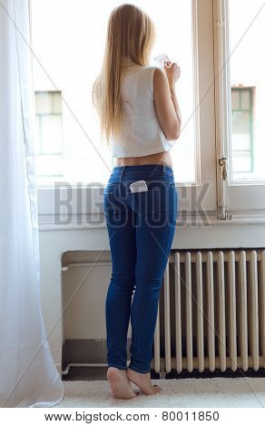 Young Beautiful Woman At Home With Mobile Phone In Back Pocket.