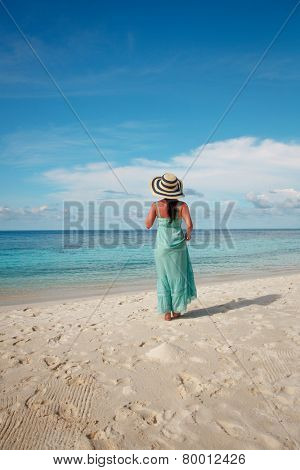 Beach vacation. Girl walking along a tropical beach in the Maldives.