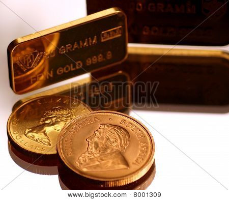 gold ounces and krugerrand coin positioned on a mirror poster