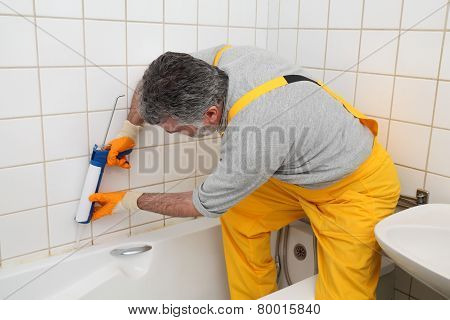 Worker Caulking Bath Tube And Tiles