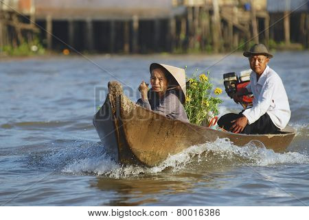 Old couple cross Mekong river by motorboat, Cai Be, Vietnam.