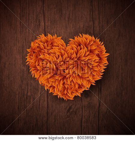 Natural background with wooden board and heart made of autumn l