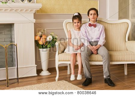 Portrait of happy little siblings sitting together on couch