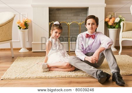 Two children is having fun while sitting on floor