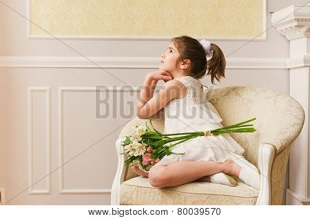 ortrait of happy little girl in white dress, sitting on couch.
