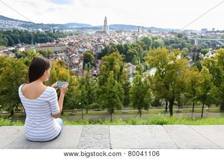 Tourist with smart phone camera in Bern, Switzerland at Rosengarten, the Rose Garden view. Woman taking photograph with smartphone at enjoying view of Berne landmarks and tourist attractions.