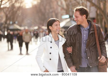 Urban couple walking on La Rambla Barcelona arm in arm. Romantic laughing lovers talking holding hands on date. Young multicultural couple Asian and Caucasian on La Rambla Barcelona, Catalonia, Spain.