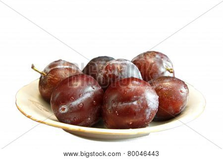 Fresh Ripe Black Plums In A White Plate Isolated On White Background
