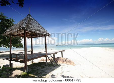 Small Hut On White Beach And Blue Sky