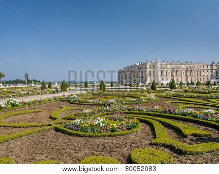 VERSAILLES FRANCE - AUGUST 28 2013: Fancy flowerbed in Versailles garden with Versailles Palace in the background, Versailles, France