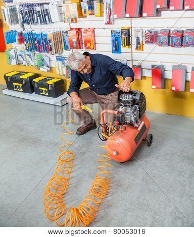 Full length of senior man examining air compressor in hardware shop